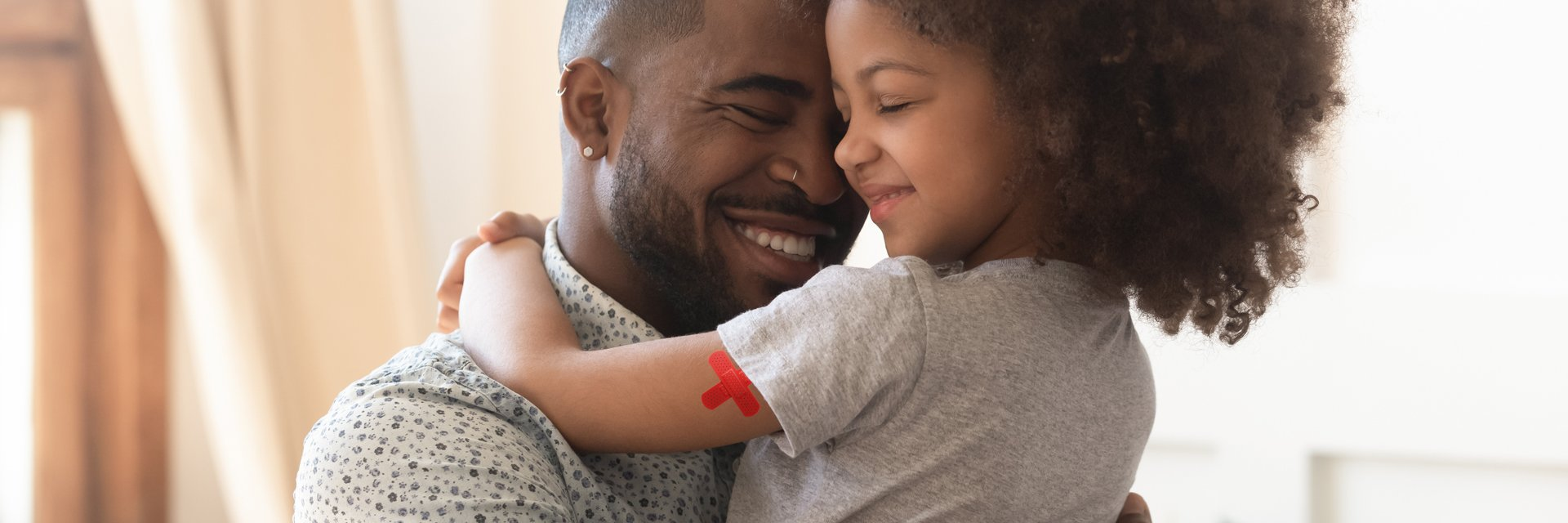 Man holding daughter with band-aid on arm.